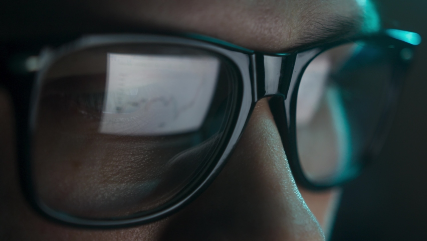 Businessman working at night looking at monitor, reflections in eyeglasses. Person stock market trader using laptop at office or home office. Business concept. Distance work. Royalty-Free Stock Footage #1065760873