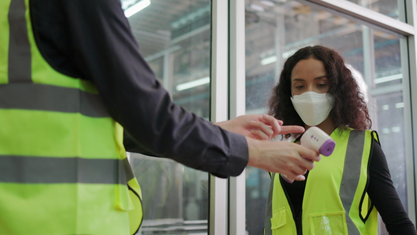 Construction worker put on face mask and Face Shield used body temperature monitor on factory Staff. Prevent COVID-19 Coronavirus and Dust PM2.5 In the industrial plant. Concept Health care Royalty-Free Stock Footage #1065766480