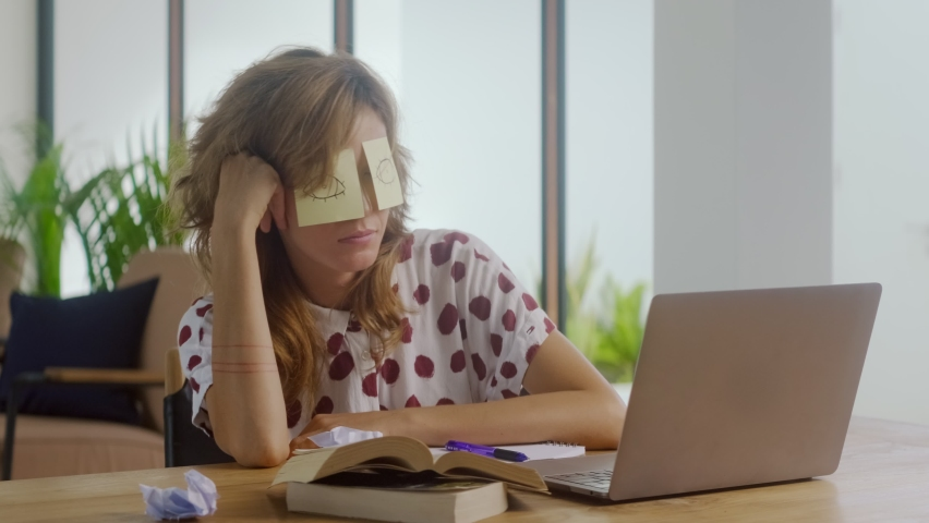 Funny lazy office worker napping at workplace covering eyes with sticky notes. Inefficient tired female employee pretends working sleeping with stickers on face sits at desk. Cheating to sleep concept Royalty-Free Stock Footage #1065768754