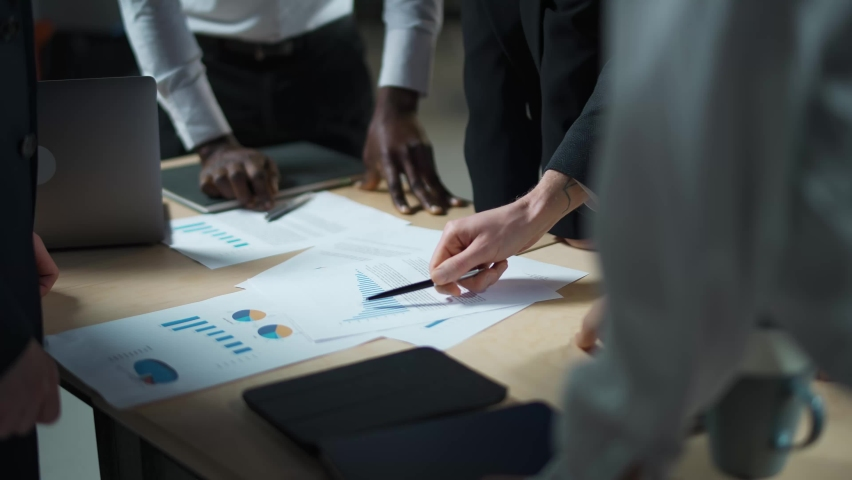 Business meeting, international management team at work, team is standing next to a work table and works with documents, discussing work plans and planning financial statistics, brainstorm. | Shutterstock HD Video #1065798067
