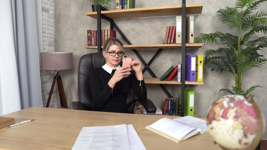 A beautiful girl works in the office at the table, a girl with a phone, a blonde works, a girl makes a selfie on the phone at a workplace Royalty-Free Stock Footage #1065799072