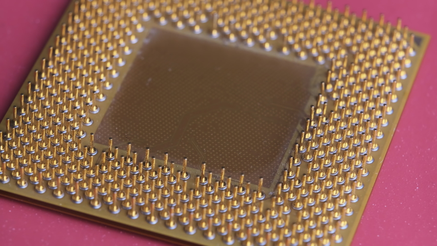 The old computer processor spins on a red background. CPU. Gold plated contacts of the microprocessor. Close-up. Chip processor computer. Central processor unit pins. Old model. Macro. Microchip Royalty-Free Stock Footage #1065811732