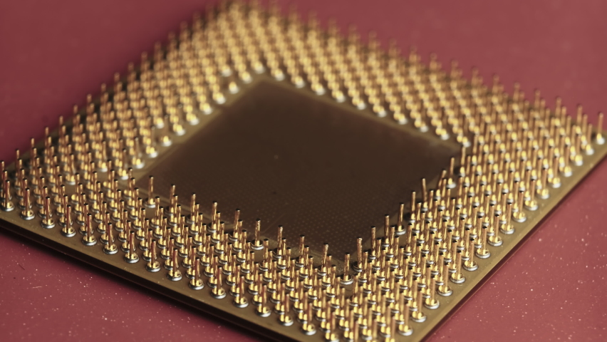 The old computer processor spins on a red background. CPU. Gold plated contacts of the microprocessor. Close-up. Chip processor computer. Central processor unit pins. Old model. Macro. Microchip Royalty-Free Stock Footage #1065811741