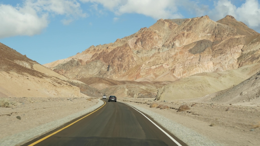 Road trip to Death Valley, Artists Palette drive, California USA. Hitchhiking auto traveling in America. Highway, colorful bare mountains and arid climate wilderness. View from car. Journey to Nevada. | Shutterstock HD Video #1065812671