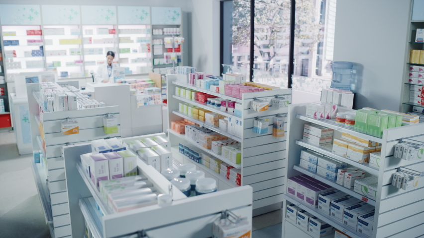Big Modern Pharmacy Drugstore with Shelves full of Packages Full of Modern Medicine, Drugs, Vitamin Boxes, Pills, Supplements, Health Care Products. Pharmacist Standing at Counter. Establishing Shot Royalty-Free Stock Footage #1065814396