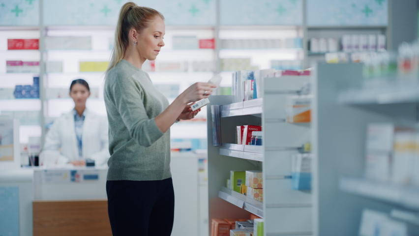 Pharmacy Drugstore: Beautiful Young Woman Chooses to Buy Medicine, Drugs, Vitamins, Searches Shelves for the Best Choice. Modern Pharma Store Shelves with Health Care, Beauty Products Royalty-Free Stock Footage #1065814507