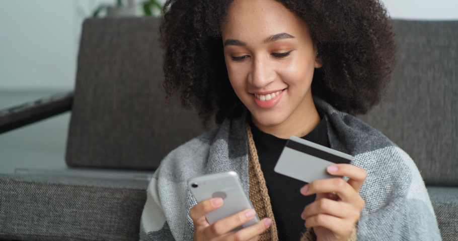 Portrait smiling afro american woman makes online purchase through mobile phone holds smartphone in her hands and credit bank card buys goods books travel ticket orders food delivery home by courier Royalty-Free Stock Footage #1065821020