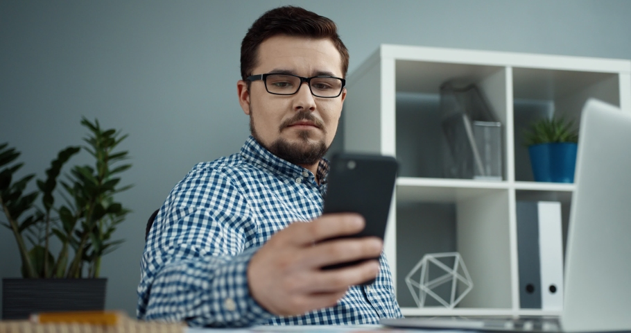 Young office manager in glasses with beard sits in modern office and responds to message on his smartphone. Royalty-Free Stock Footage #1065822160