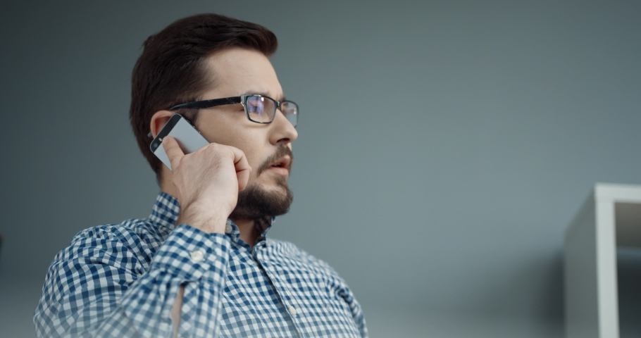 Close up of caucasian businessman with glasses sitting in office and giving orders while talking on mobile phone. Royalty-Free Stock Footage #1065822166