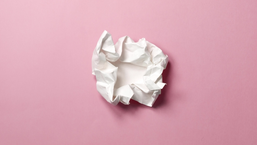Stop motion animation paper wrinkles making a paper ball. Pink background. A paper ball spreads making a blank sheet and folds again until it disappears. Royalty-Free Stock Footage #1065825376