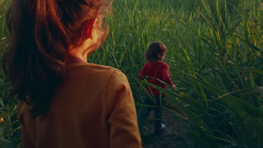 Children: sister and brother play catch-up through the tall grass, along the river, through the tropical jungle. Rear view of a running child. The kid runs after his sister on the road. Toddlers