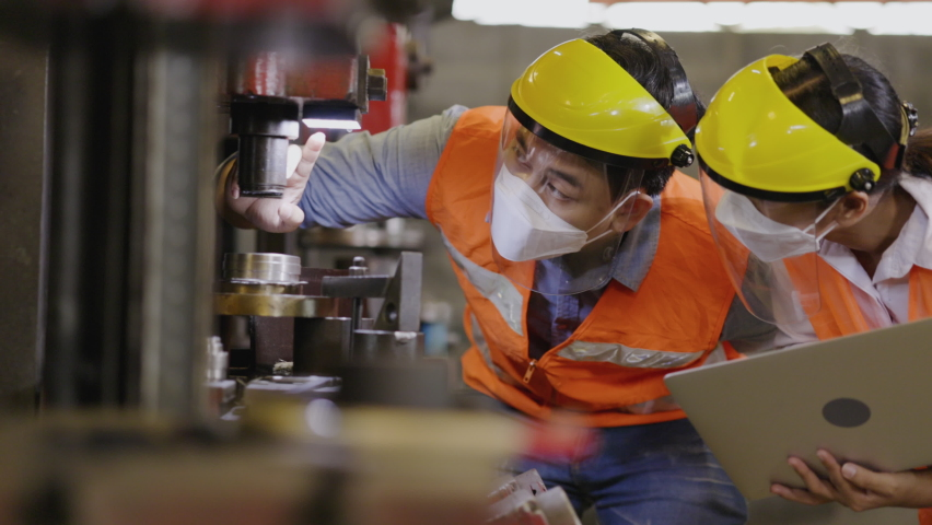 Asian machine engineer put on mask and face shield while working in an industrial plant. Safety in the work to prevent COVID-19 and Dust PM2.5. Work as team based on technology to check equipment. Royalty-Free Stock Footage #1065831973