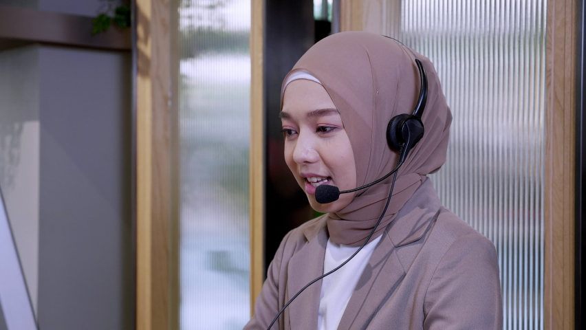 Beautiful woman in hijab at the computer with headset, distant work, call center. Confident islam woman worker in call center crossed arms face camera smiling joyful operator and helps with the order. Royalty-Free Stock Footage #1065855022