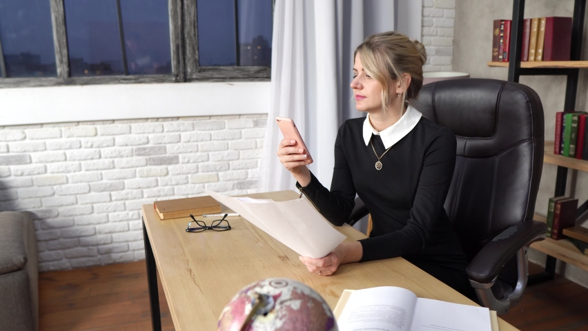 Pretty girl working in the office, girl with phone Royalty-Free Stock Footage #1065863692