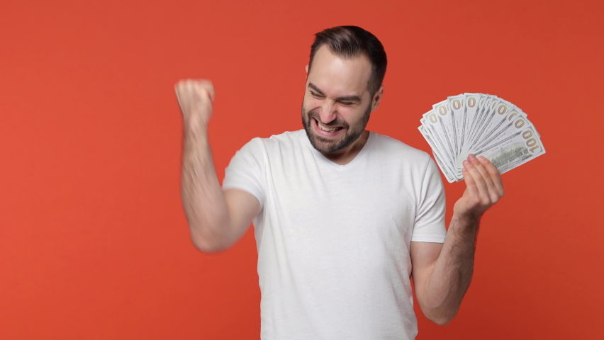 Happy overjoyed bearded young man 20s in white casual t-shirt isolated on orange background studio. People lifestyle concept. Hold fan cash money in dollar banknotes doing winner gesture celebrating Royalty-Free Stock Footage #1065865639