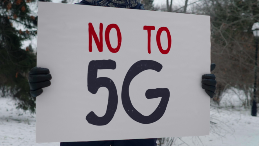 A man is standing in the park with a banner No To 5G. Black and red writing. The protest is against the implementation of the newest cellular network and is based on unproven conspiracy theories. | Shutterstock HD Video #1065882523