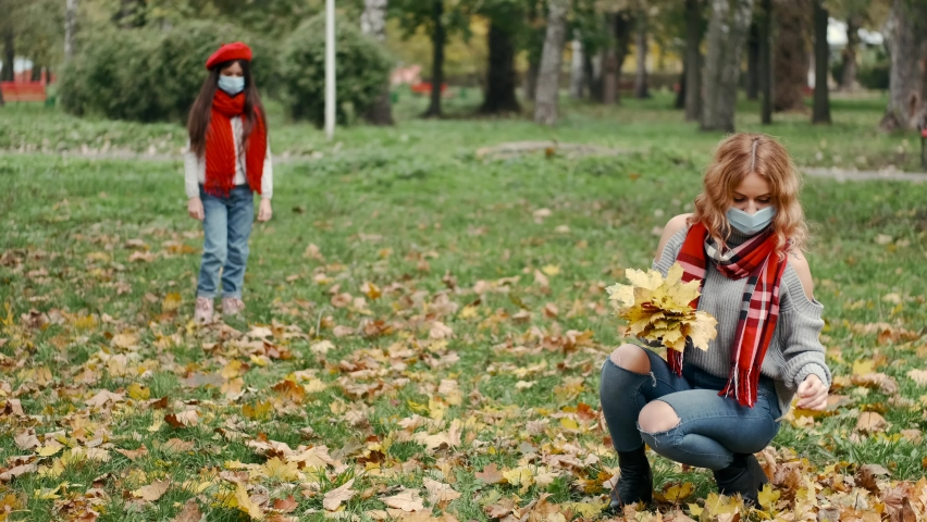Mother and daughter having fun in autumn park. The kid is wearing hat and scarf and disposable mask during qurantine. Mother in mask is siotting and picking up golden maple leaves. People, covid-19 | Shutterstock HD Video #1065885520