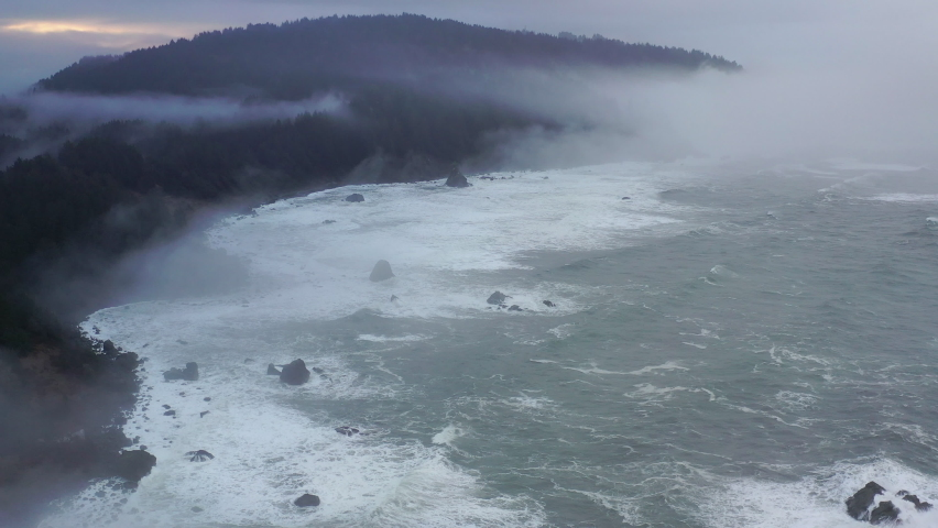 Coming off the Pacific Ocean, the foggy marine layer drifts over the Northern California coastline in Klamath. The scenic Pacific Coast Highway runs along this amazing part of the west coast. Royalty-Free Stock Footage #1065886813
