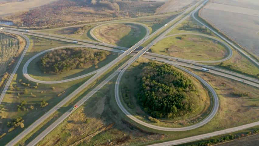 Sunset traffic navigates through Interstate 39 , 80 cloverleaf interchange near Peru, Illinois.   Shutterstock HD Video #1065893422