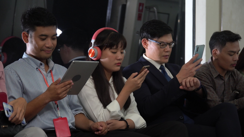 Group of happy asian people passenger using smartphone  and digital tablet sitting in subway . social media addiction concept. crowd with Communication device in Public Transport in city lifestyle . | Shutterstock HD Video #1065894556