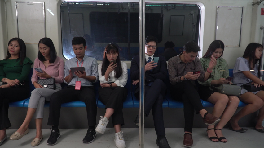 Group of happy asian people passenger using smartphone  and digital tablet sitting in subway . social media addiction concept. crowd with Communication device in Public Transport in city lifestyle . | Shutterstock HD Video #1065894562