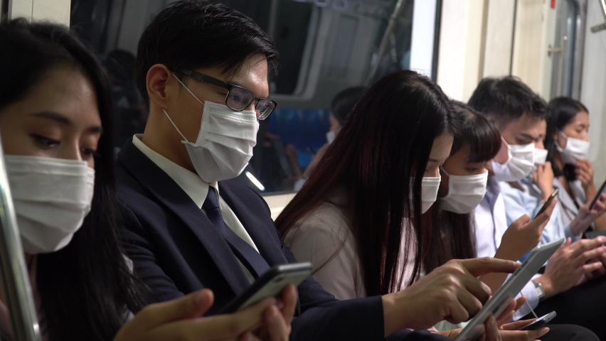 Asian business people wearing surgical mask using smartphone sitting close together in subway no social distancing not afraid infection of coronavirus. not follow new normal in Public Transport  | Shutterstock HD Video #1065894580