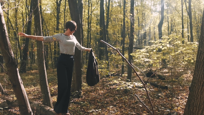 Beautifull tall woman in stylish wear walks in the forest. She enjoys the warmth of pretty autumn sunset. | Shutterstock HD Video #1065895747