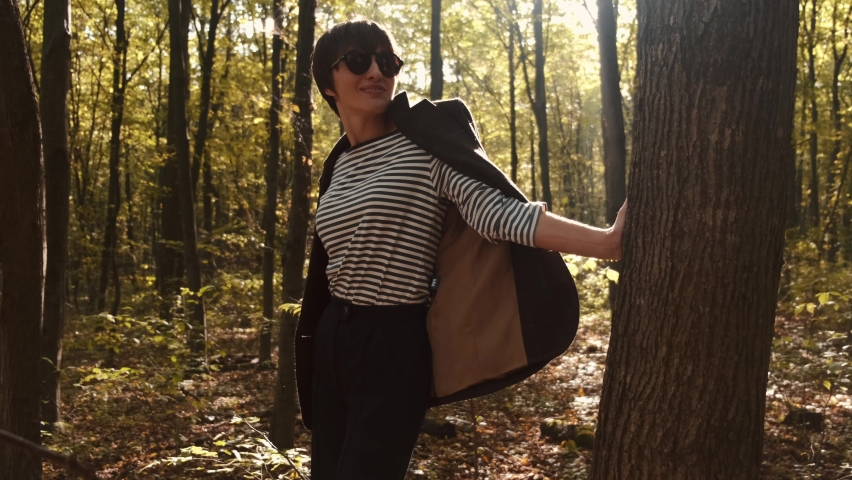 Beautifull tall woman in stylish wear walks in the forest. She enjoys the warmth of pretty autumn sunset. | Shutterstock HD Video #1065895906