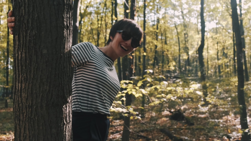 Beautifull tall woman in stylish wear walks in the forest. She enjoys the warmth of pretty autumn sunset. | Shutterstock HD Video #1065895948