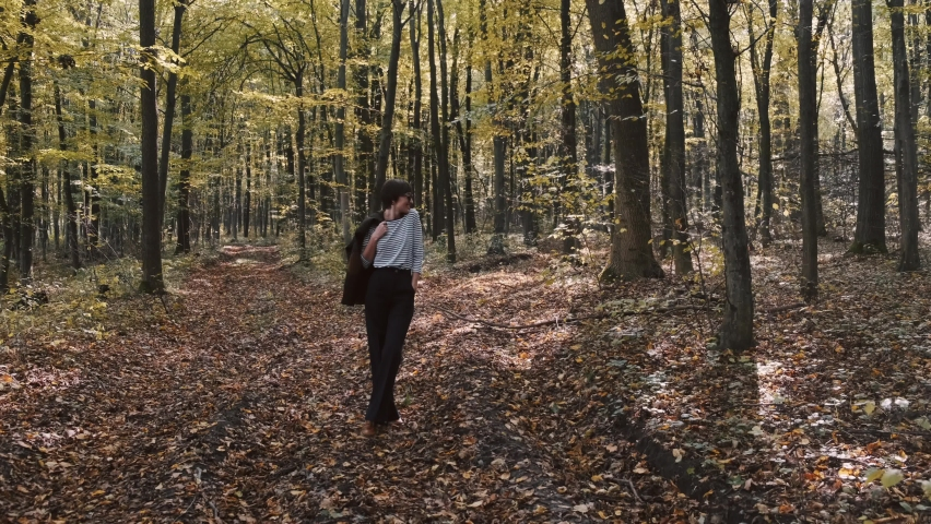 She walks in blue jeans along path park, through forest, strewn fallen autum dry yellow leaves. Leisurely walk fresh air day off. A place to think, alone with your thoughts. Peaceful state | Shutterstock HD Video #1065895960