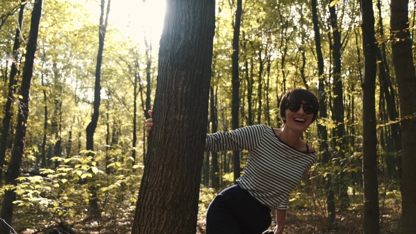 Beautifull tall woman in stylish wear walks in the forest. She enjoys the warmth of pretty autumn sunset. | Shutterstock HD Video #1065896002