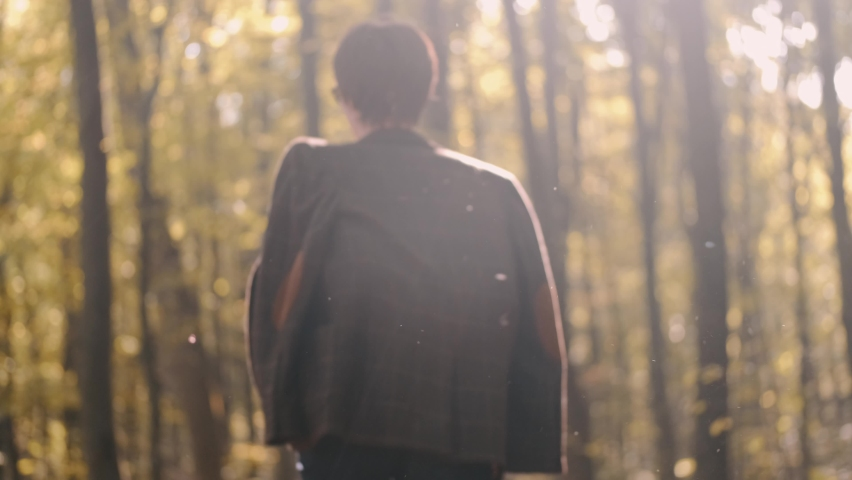 She walks in blue jeans along path park, through forest, strewn fallen autum dry yellow leaves. Leisurely walk fresh air day off. A place to think, alone with your thoughts. Peaceful state | Shutterstock HD Video #1065896011