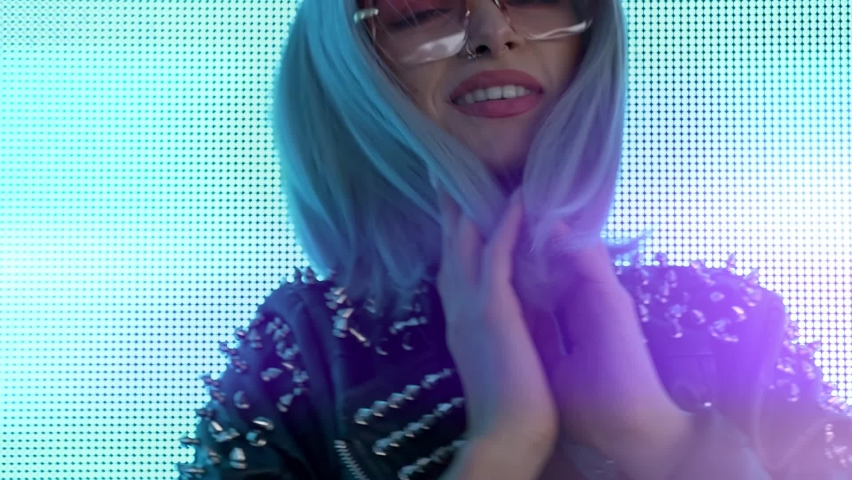 Cinematic video of a beautiful young woman posing against a led panel. Teenager with alternative futuristic cyberpunk look dancing and having fun into light streams.  | Shutterstock HD Video #1065896725