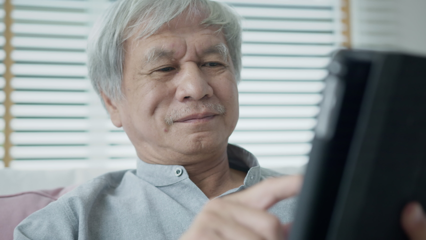 Candid old asian retired guy use tablet computer to transfer money online or financial payment and read text, smile or laugh with happy and positive. Senior asia with digital technology concept. | Shutterstock HD Video #1065898021
