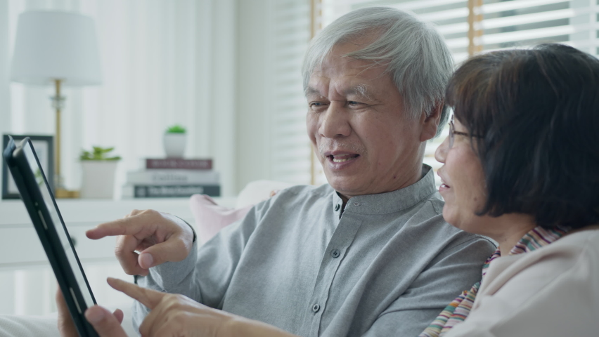 Candid old asian retired couple use tablet computer to transfer money online or financial payment and read text, smile or laugh with happy and positive. Senior asia with digital technology concept. | Shutterstock HD Video #1065898024