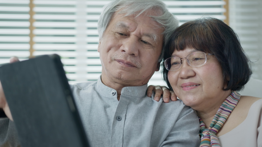 Candid old asian retired couple use tablet computer to transfer money online or financial payment and read text, smile or laugh with happy and positive. Senior asia with digital technology concept. | Shutterstock HD Video #1065898030