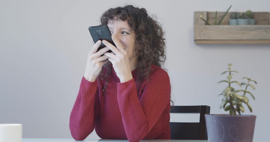 Smiling woman at home recording an audio message with a smart phone | Shutterstock HD Video #1065898282