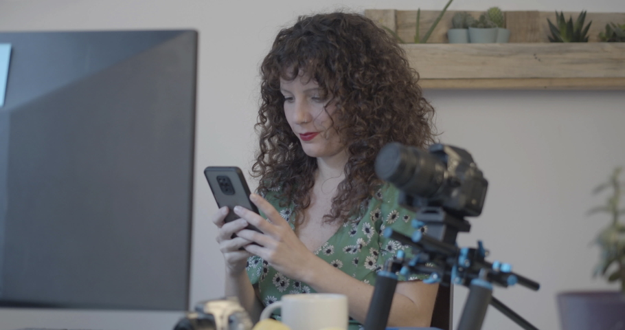 Smiling journalist in an office recording an audio message with a smartphone | Shutterstock HD Video #1065898312
