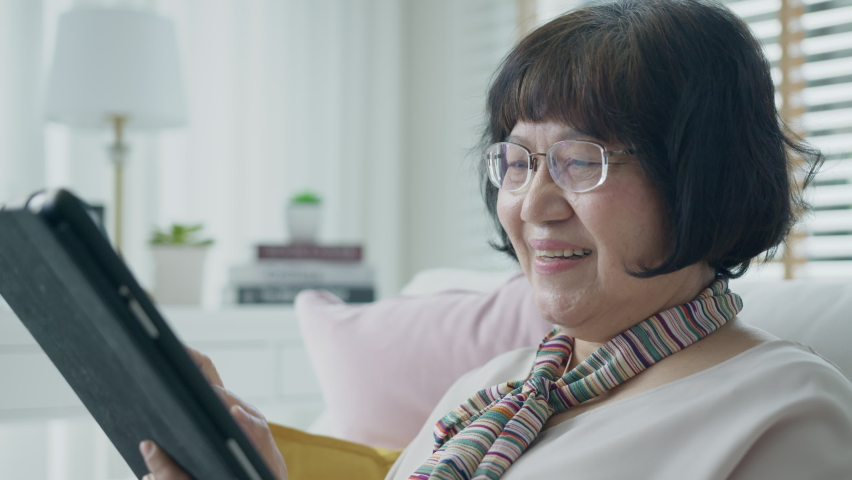 Candid old asian retired lady use tablet computer to transfer money online or financial payment and read text, smile or laugh with happy and positive. Senior asia with digital technology concept. | Shutterstock HD Video #1065898351