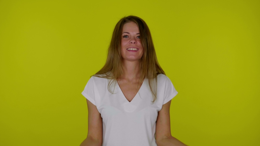 Cheerful smiling woman in white T-shirt dancing with red and blue donuts in hands on yellow background with copy space. Place for text or product. 4K slow motion footage | Shutterstock HD Video #1065898414