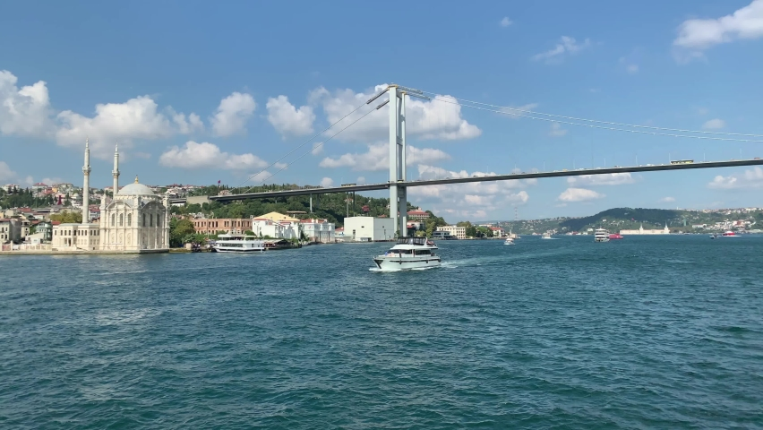 """Footage of luxury yacht passing on Bosphorus in Istanbul. Historical landmark called """"Ortakoy Mossque"""" and bridge are in the view. Beautiful scene. It is a cloudy sunny summer day. 