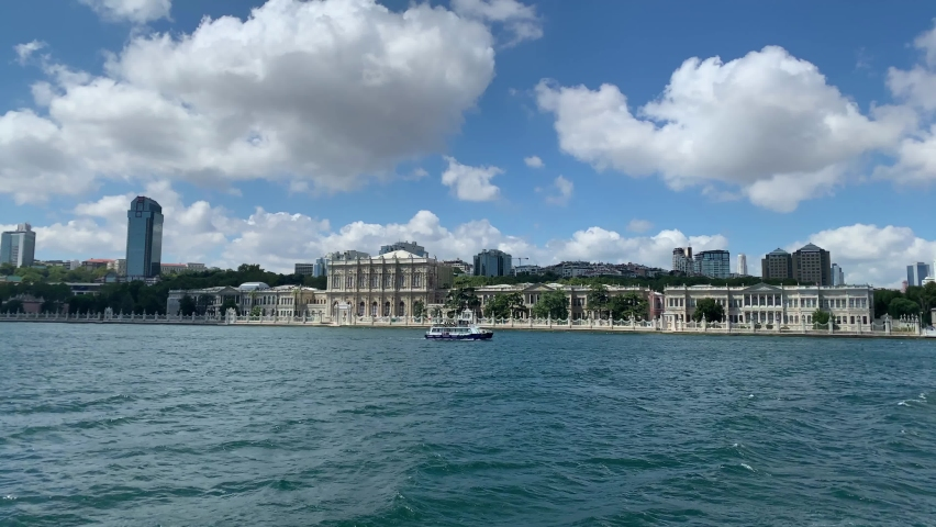 """Footage of a cruise tour boat passing and historical palace called """"Dolmabahce"""" by Bosphorus and cityscape of European side in Istanbul. It is a sunny cloudy summer day. Camera moves forward. 