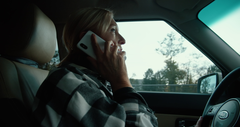 Distracted middle-aged woman talking on phone while driving car, unsafe driving | Shutterstock HD Video #1065900400
