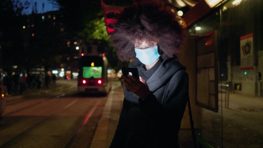 Woman wearing face mask using smart phone in city at night . Italy | Shutterstock HD Video #1065901411