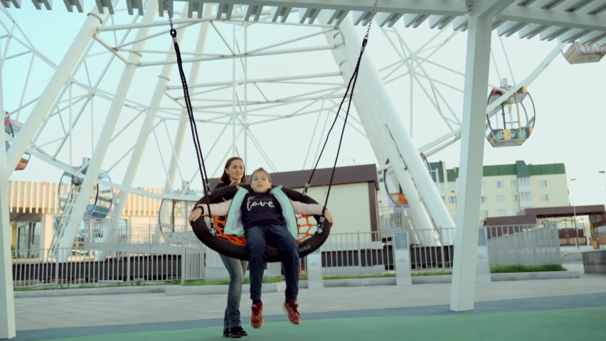 Young woman and young girl swing on a swing in the city square. | Shutterstock HD Video #1065902905