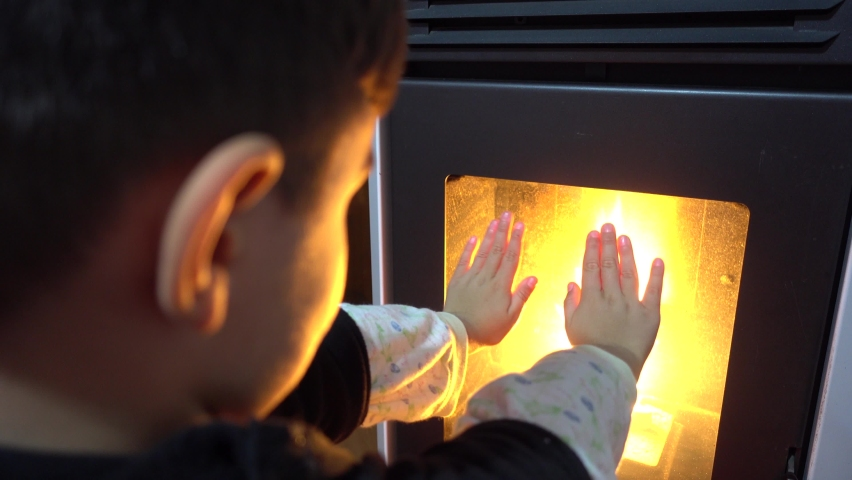 4K Boy warms up his hands against the fire in furnace
