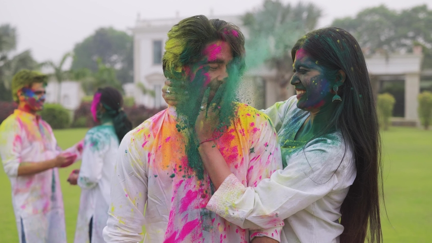 A shot of a young beautiful smiling woman comes from behind and surprises a handsome man by applying color on his face. An attractive Indian couple celebrating Holi festival with friends outdoors. Royalty-Free Stock Footage #1065932341