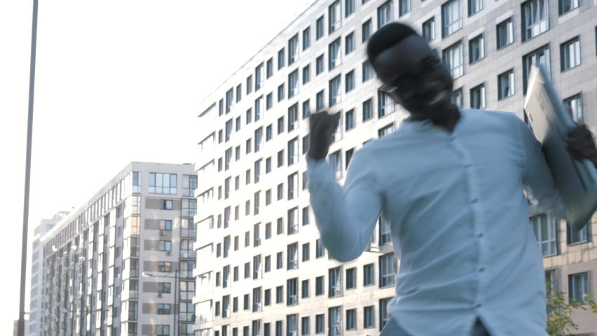 Amazed happy businessman receiving sms message reading good news. Excited overjoyed male winner celebrating dancing outdoors near office building, success, real joyful emotions, excited black man at   Shutterstock HD Video #1065934327