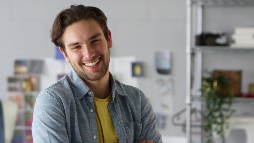 Portrait of smiling male clothes designer by desk in fashion studio - shot in slow motion   Shutterstock HD Video #1065942964
