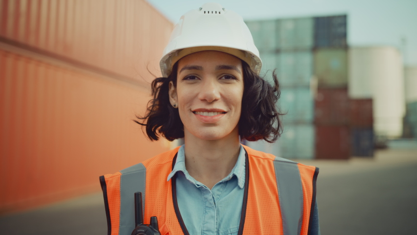 Smiling Portrait of a Beautiful Hispanic Female Industrial Engineer in White Hard Hat, Safety Vest and with Two-Way Radio Working in Logistics Center. Inspector or Supervisor in Container Terminal.
